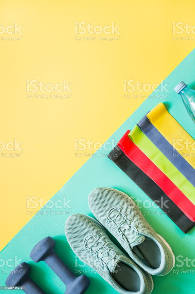 Sport and fitness equipment, rubber band, dumbbells, fitness shoes on...