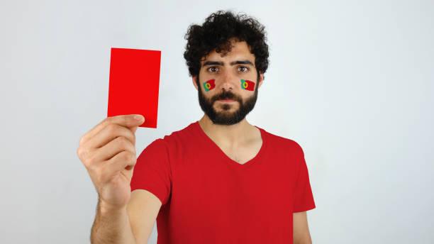 sportfläkt som håller ett rött kort. - football portugal flag bildbanksfoton och bilder