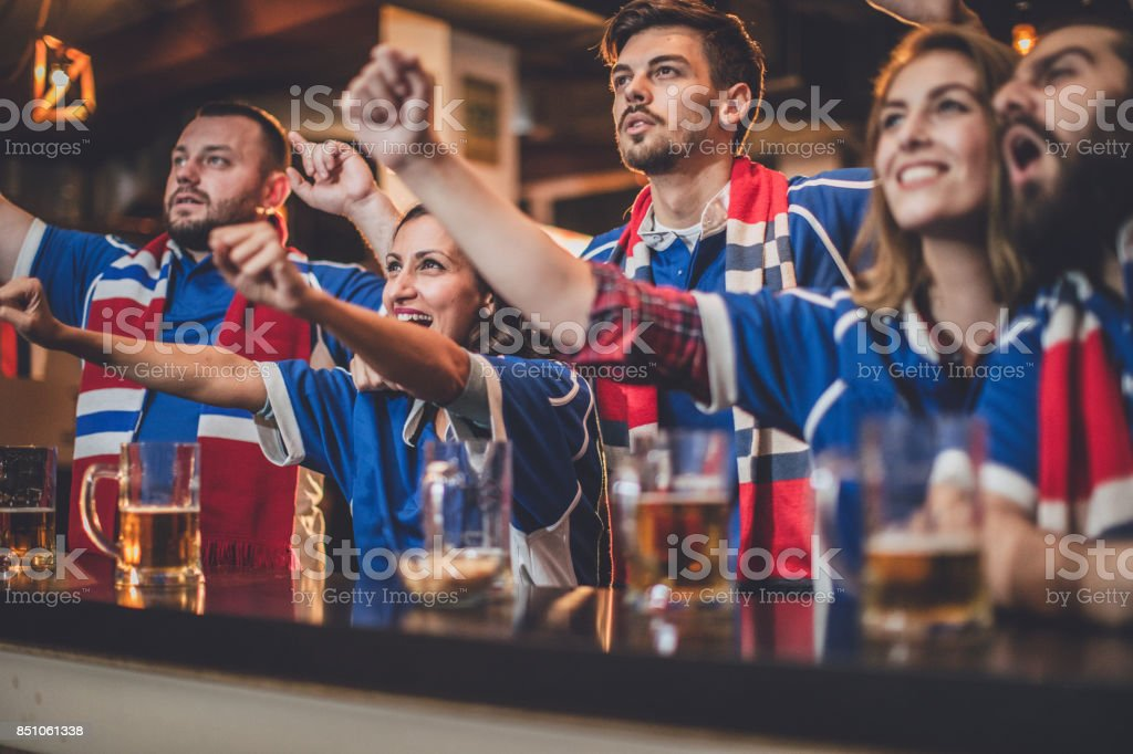Group of young people, sitting in a pub all together, watching a...