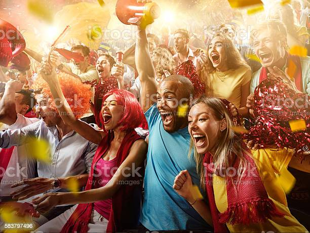 :biggrin:On the foreground a group of cheering fans watch a sport championship on stadium. Everybody are happy. People are dressed in casual cloth. Colourful confetti flies int the air.