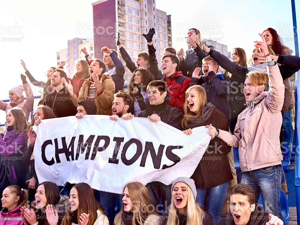 Sport fans keep champion banner on tribunes. stock photo