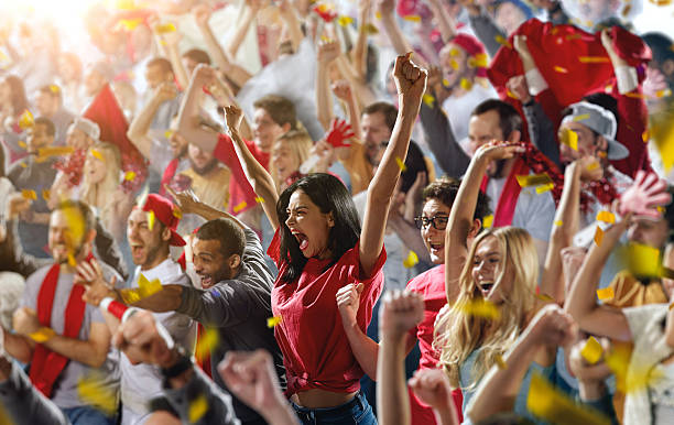 Sport fans On the foreground a group of cheering fans watch a sport championship on stadium. One girl stands with his hands up to the sky. People are dressed in casual cloth. spectator stock pictures, royalty-free photos & images