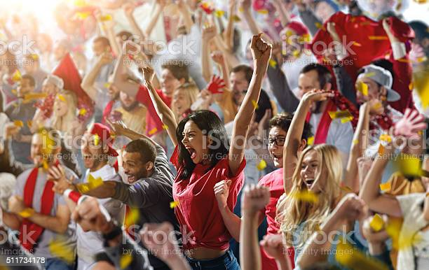 On the foreground a group of cheering fans watch a sport championship on stadium. One girl stands with his hands up to the sky. People are dressed in casual cloth.