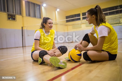 Beautiful young women preparing for the volleyball game indoors,sitting on the floor and laughing