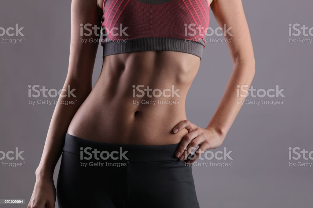 Sport, fit woman. Female with perfect abdomen muscles on grey background. Dieting, fitness, active lifestyle concept, copy space stock photo