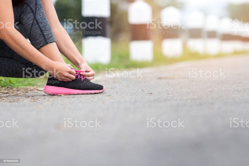 sport, fitness, people and lifestyle concept - close up of woman tying shoelaces outdoors royalty-free stock photo