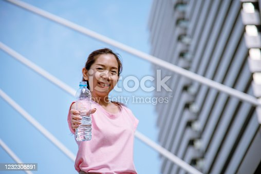 930998708 istock photo Sport Fitness Women drinking mineral water after running exercise modern city wear wellness sportswear outside. Young woman workout outdoor exercising outside. Healthy wellness lifestyle woman concept 1232308891