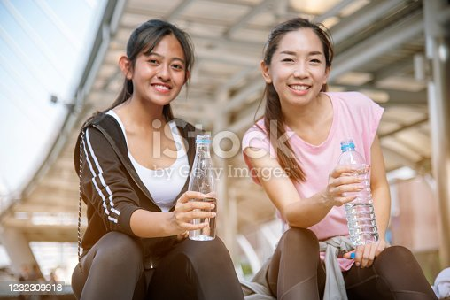 930998708 istock photo Sport Fitness Women drinking mineral water after running exercise modern city wear wellness sportswear outside. Young woman workout outdoor exercising outside. Healthy wellness lifestyle woman concept 1232309918