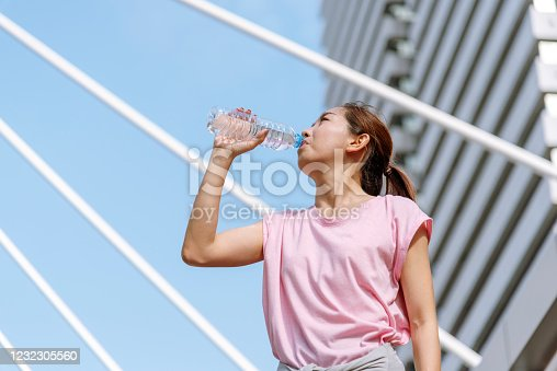 930998708 istock photo Sport Fitness Women drinking water in modern city wear wellness sportswear outside. Young woman workout outdoor exercising on bright sunny outside. Healthy wellness lifestyle woman concept. 1232305560