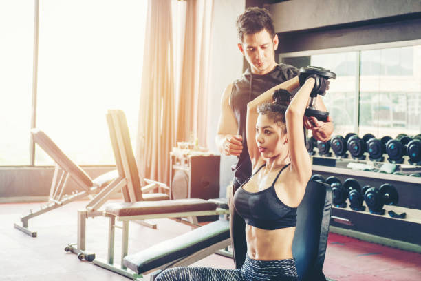 Sport girl doing weight exercises  working with heavy dumbbells  her personal trainer at Gym workout stock photo