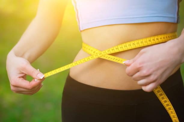 sport mädchen messen taille mit gelben maßband. reduzierung von übergewicht - taillentrainer stock-fotos und bilder