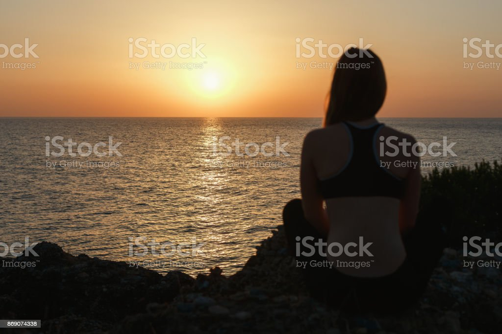 Sport girl meditating by the sea at sunset stock photo