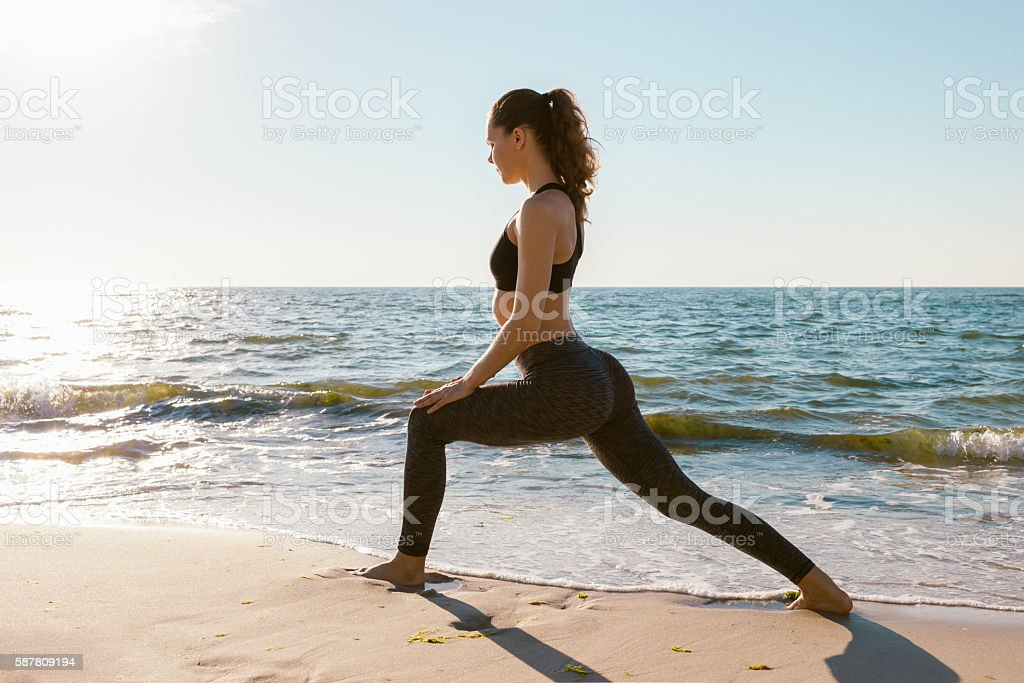Sport girl on a beach doing lunges exercises stock photo