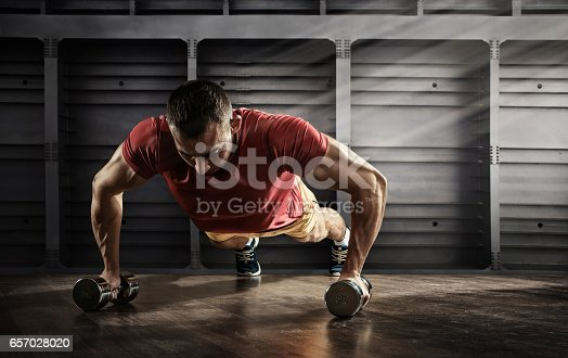 istock Sport. Handsome man doing push ups exercise with one hand in fitness gym 657028020