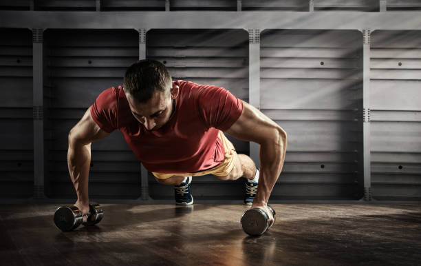 Sport. Handsome man doing push ups exercise with one hand in fitness gym stock photo