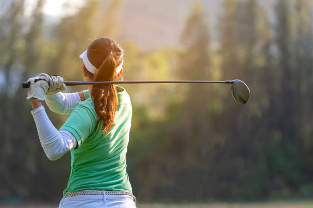 sport healthy. asian sporty woman golf player doing golf swing tee off on the green sunset evening time, she presumably does exercise. healthy and lifestyle concept. - golf foto e immagini stock