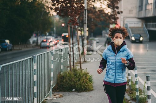 Sportswoman jogging with protective face mask for illness prevention against COVID-19