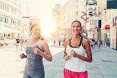 Two girls jogging in the city