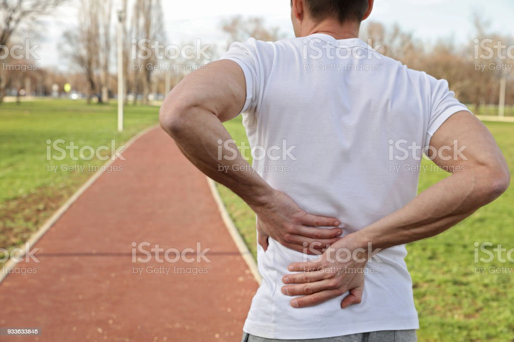 Sport injury, Man with back pain. Pain relief and health care concept. stock photo