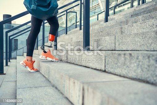 Sport is my way of life. Cropped photo of woman with leg prosthesis in sports clothing carrying her sport bag while standing on stairs outdoors. Disabled sport concept.