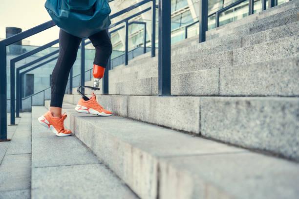 idrotten är mitt sätt att leva. beskurna foto av kvinna med benprotes i sportkläder bär hennes sport väska stående på trappor utomhus. - protesutrustning bildbanksfoton och bilder