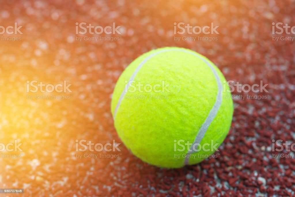 Tennis balls in red court. Tennis is racket sport that can be played...