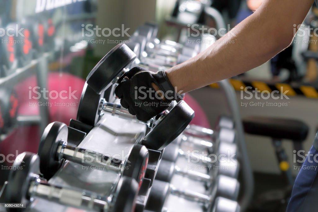 Homem de esporte fazendo linhas de haltere de um braço de metal no ginásio. - foto de acervo
