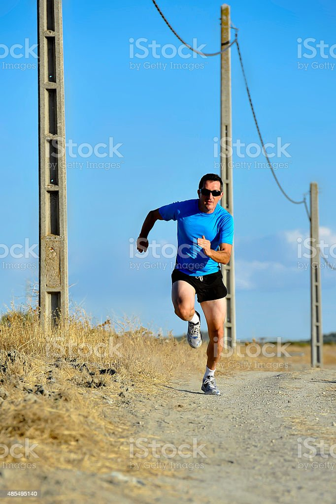 sport man running on countryside track with power line poles stock photo