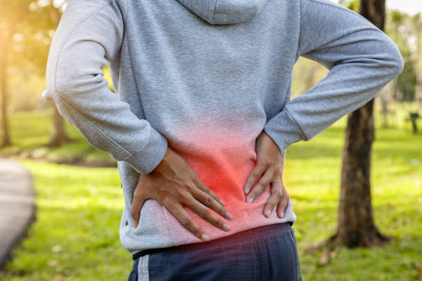 sport man suffering from backache at park outdoors, lower back pain concept - dolore fisico foto e immagini stock
