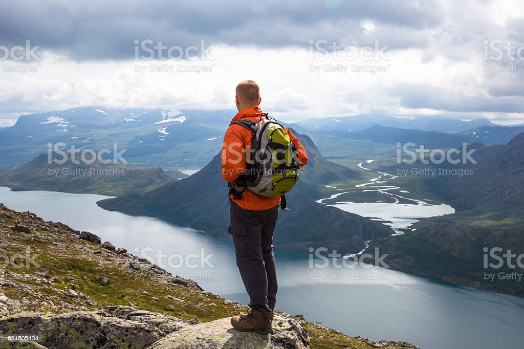 Sport mane hiking on Besseggen. Hikers enjoy beautiful lake and foto stock royalty-free