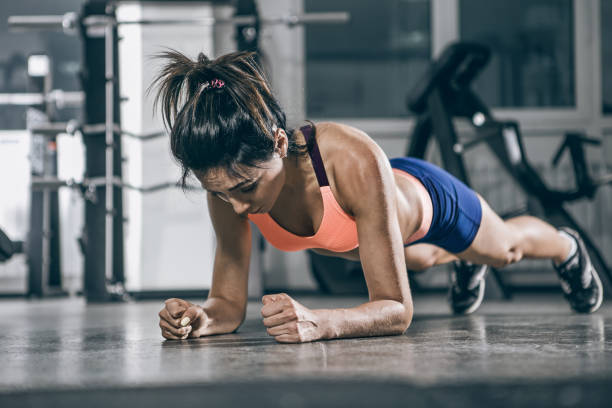 Sport. Muscular woman on a plank position. stock photo