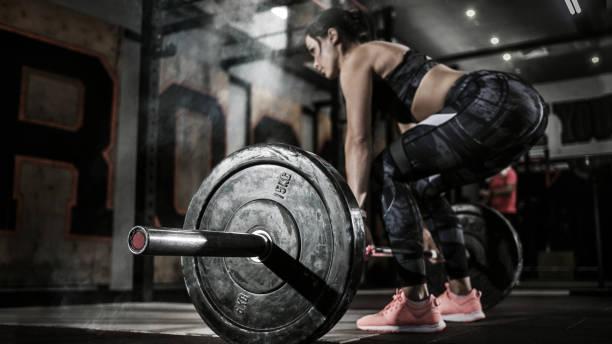 deporte. mujeres musculosas levantando peso muerto en el gimnasio con barbell. interior dramático con humo. - culturismo fotografías e imágenes de stock