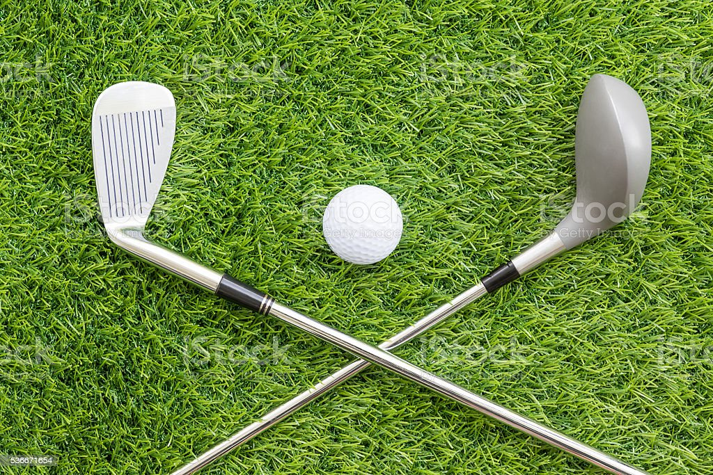 Sport objects related to golf equipment ,Golf club and ball on green...