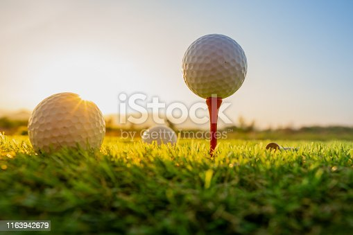 istock sport outdoor, golf ball on tee pegs ready to play in the green grass and light shines sunset 1163942679