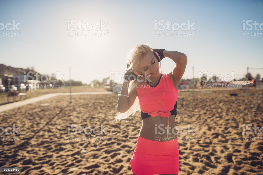 sport outdoor photo of beautiful young blonde woman in pink colorful sport suit listening to music on headphones by the beach royalty-free stock photo