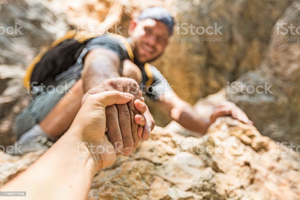 Sport. Adventurers helping each other to climb the mountain Activity Stock Photo