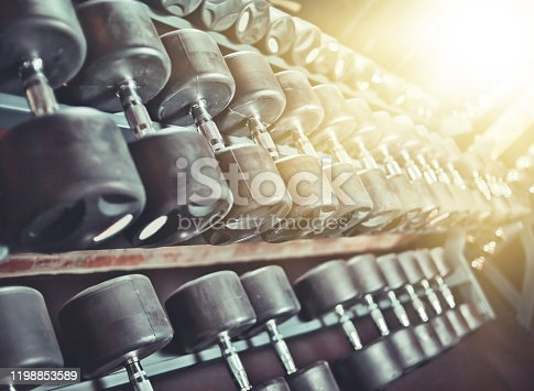 Black steel dumbbell set. Rack with many dumbbells close-up at gym