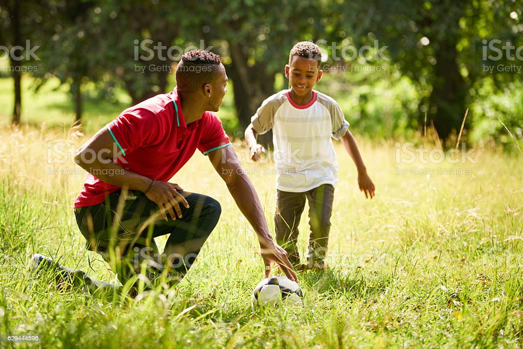 Sport Practice With Father Teaching Son How To Play Soccer stock photo