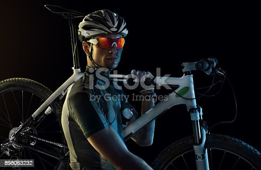 istock Sport. Professional road cyclist portrait. Sport. Isolated Cyclist carry a bike. 898063232