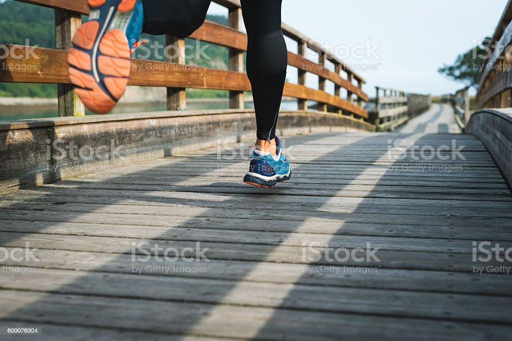 Sport running shoes closeup of man training outdoor on walkway stock photo