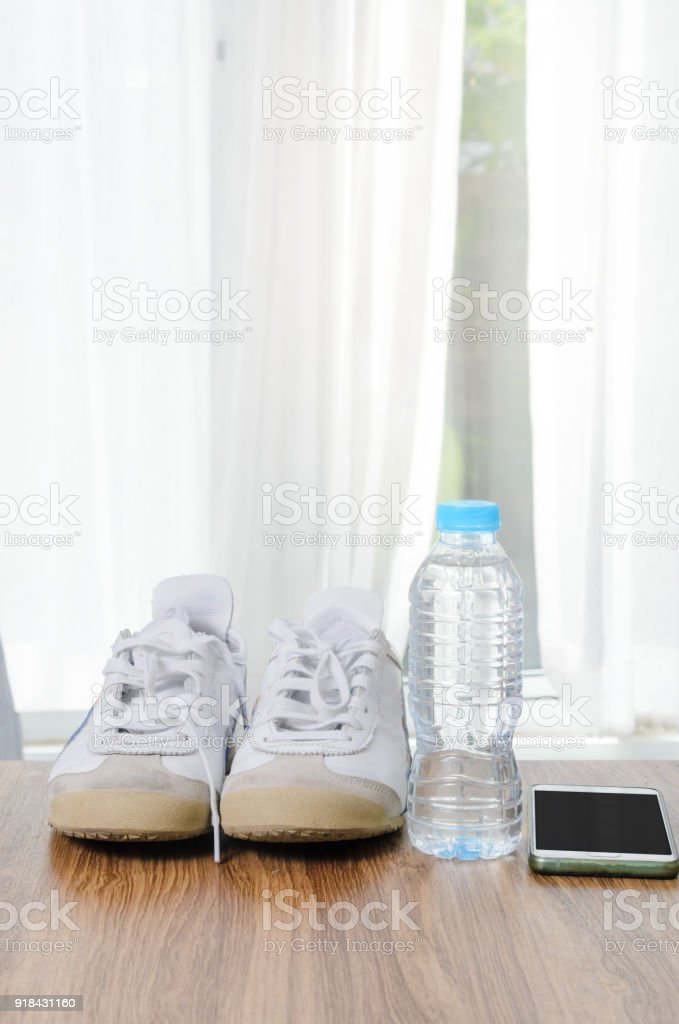 Sport shoes a bottle of water and smart phone on wooden floor, sport...