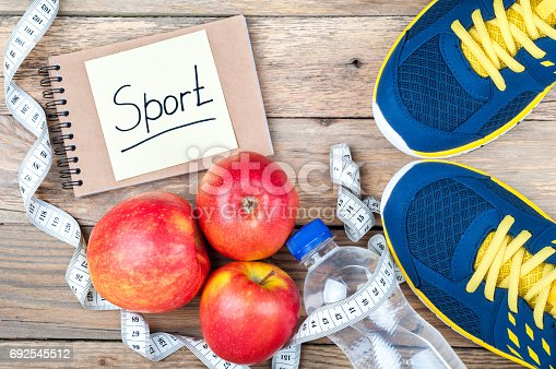 istock Sport shoes, apples, bottle of water, measuring tape and open notebook with word Sport on old wooden background. Sport equipment. Healthy lifestyle and diet concept. Top view 692545512