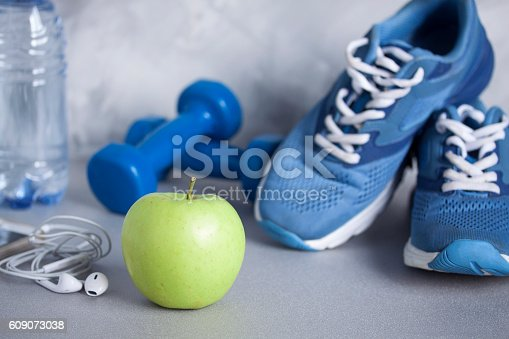 istock Sport shoes, dumbbells, earphones, apple, bottle of water, concrete background 609073038