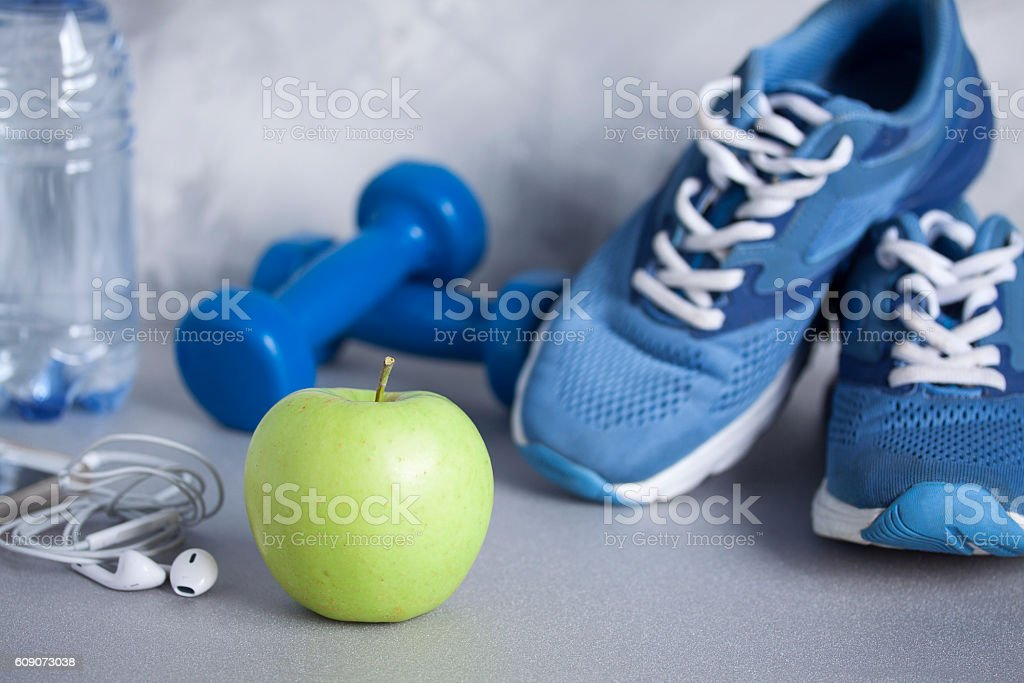 Sport shoes, dumbbells, earphones, apple, bottle of water, concrete background stock photo