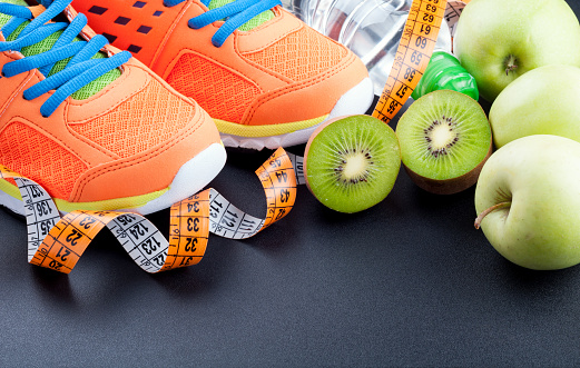 istock Sport shoes, fruits,  bottle of water and measuring tape on dark background. Sport equipment. Concept healthy life, sports and diet 692556896