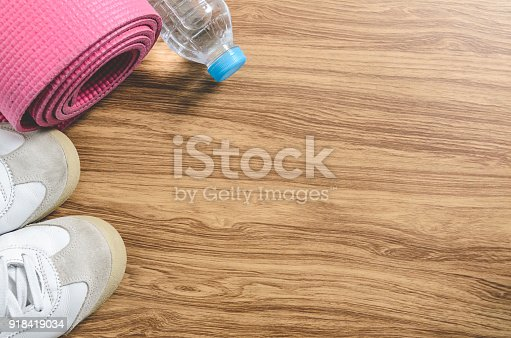istock Sport shoes yoga mat and a bottle of water on wooden background. 918419034