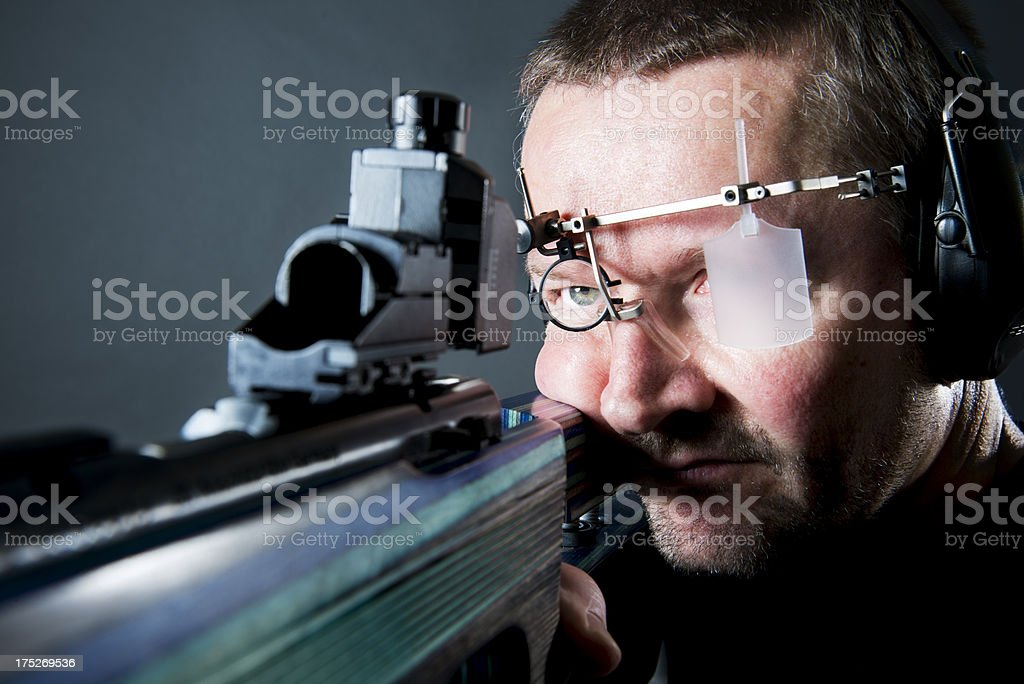 Close up portrait of a sport shooter using a 22 caliber rifle with...