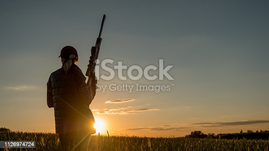 Beautiful silhouette of a woman with a rifle in the rays of the setting sun. Sports shooting and hunting concept. 4K video