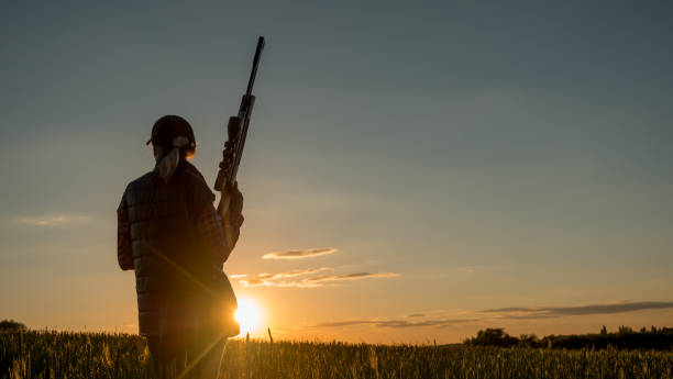 Sport shooting and hunting - woman with a rifle at sunset Beautiful silhouette of a woman with a rifle in the rays of the setting sun. Sports shooting and hunting concept. 4K video hunter stock pictures, royalty-free photos & images