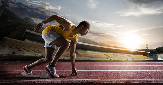 Sport Sprinter Leaving Starting Blocks On The Running Track Stock Photo - Download Image Now